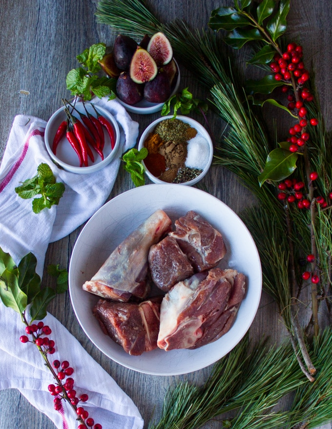 Ingredients for cooking lamb: lamb shoulder pieces cut up surrounded by a bowl of Moroccan spice, surrounded by red chillies, fresh figs and a tea towel