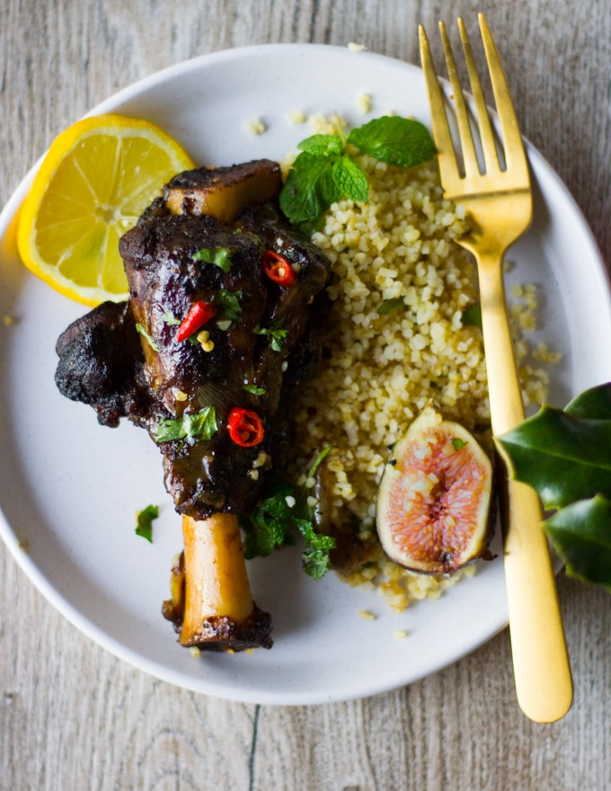 A serving plate with a piece of cooked lamb shoulder with Moroccan spice in a sweet and spice sauce surrounded by some couscous and fresh figs and a slice of lemon