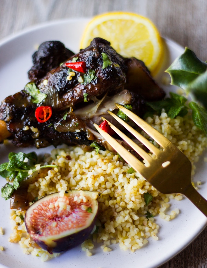 A fork eating a piece of cooked lamb with couscous and some sweet figs and spicy chillies on a plate