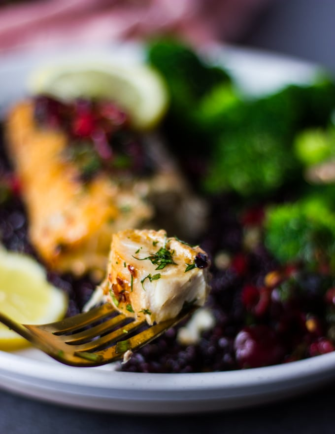 A fork showing a bite of baked mahi mahi fish texture and juicy baked fish