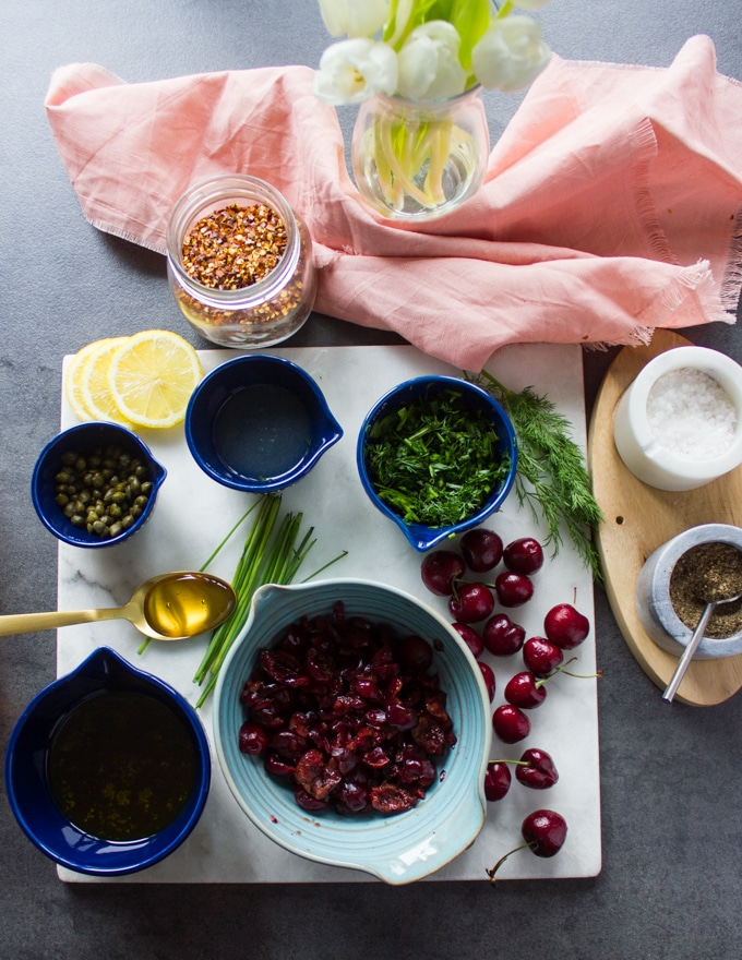 Ingredients for the cherry salsa : cherries in a bowl, salt and pepper, fresh herbs in a bowl, capers in a bowl, olive oil in a bowl, lemon juice in a bowl and a spoon of honey