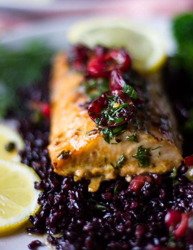 A fillet of baked mahi mahi over black rice and some cherry salsa over the top