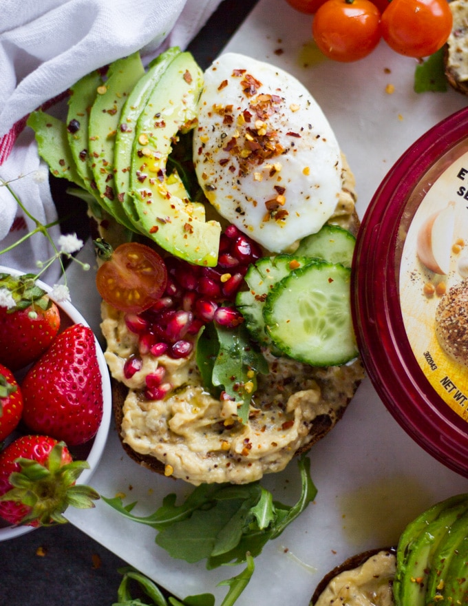 A hummus toast on rye bread with a spread of hummus, a poached egg, some sliced avocados, cucumbers, tomatoes and pomegranate arils