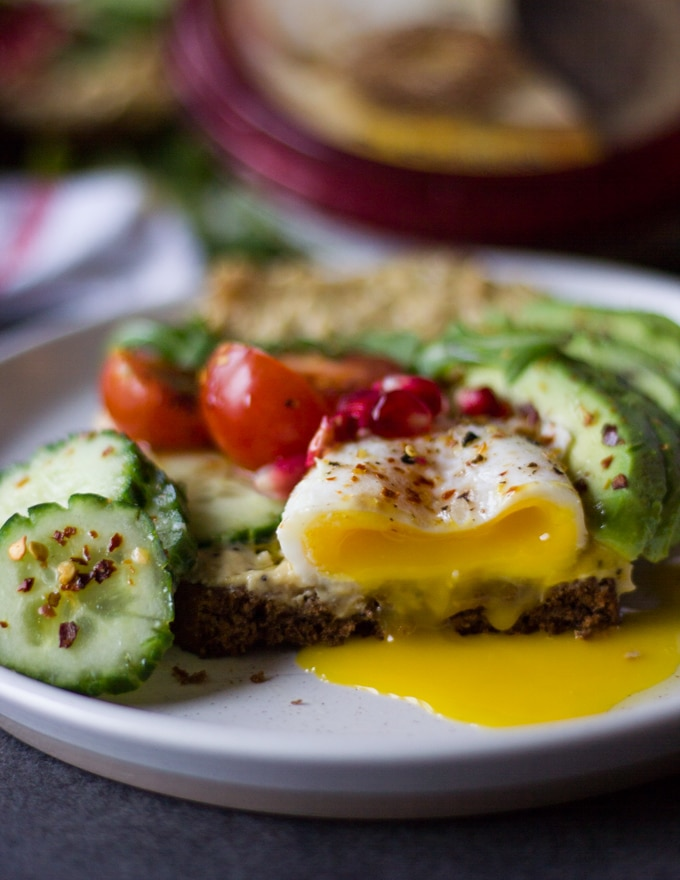 A cut through the breakfast toast showing the runny yolks from the poached egg over the hummus toast on a white plate surrounded by avocados, cucumbers and tomatoes