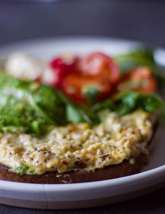 A loaded hummus toast or breakfast toast with a thick spread of hummus, some arugula, tomatoes, cucumbers, avocados and poached egg