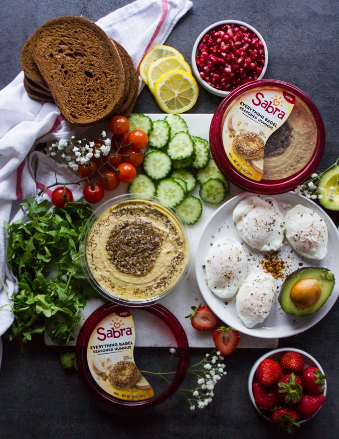 Ingredients for the hummus toast or breakfast toast on a white marble. Ingredients are a plate of poached eggs, a tub of hummus, sliced avocados, cucumbers, arugula, cucumbers, tomatoes, rye bread and some strawberries in a bowl , and lemon slices