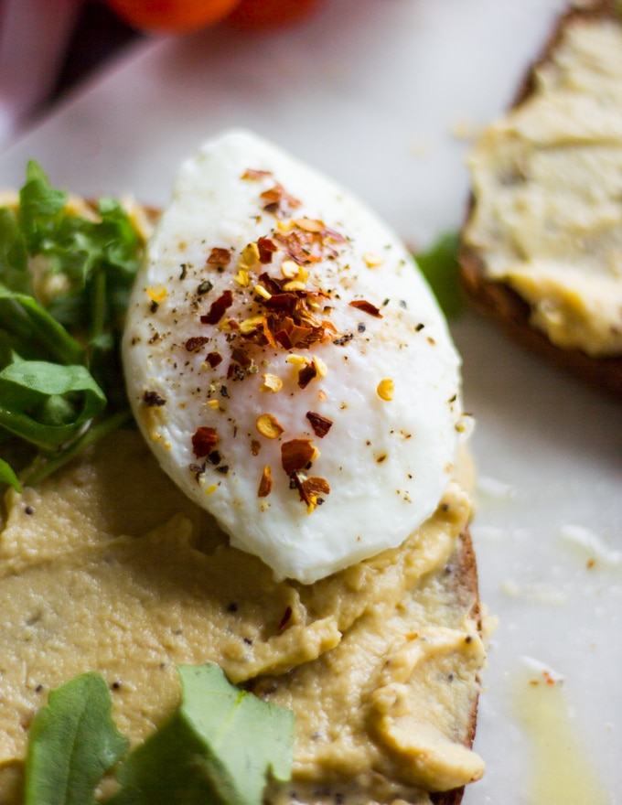 A poached egg added over the hummus layered toast with a sprinkle of salt, pepper and chilli flakes