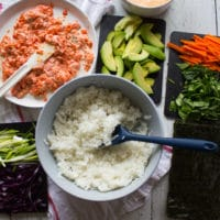 Ingredients for sushi burrito ready to assemble including a bowl of sushi rice, a spicy salmon sushi mixture, fresh vegies chopped for the sushi burrito filling such as sliced avocados, carrots, scallions, purple cabbage and spinach