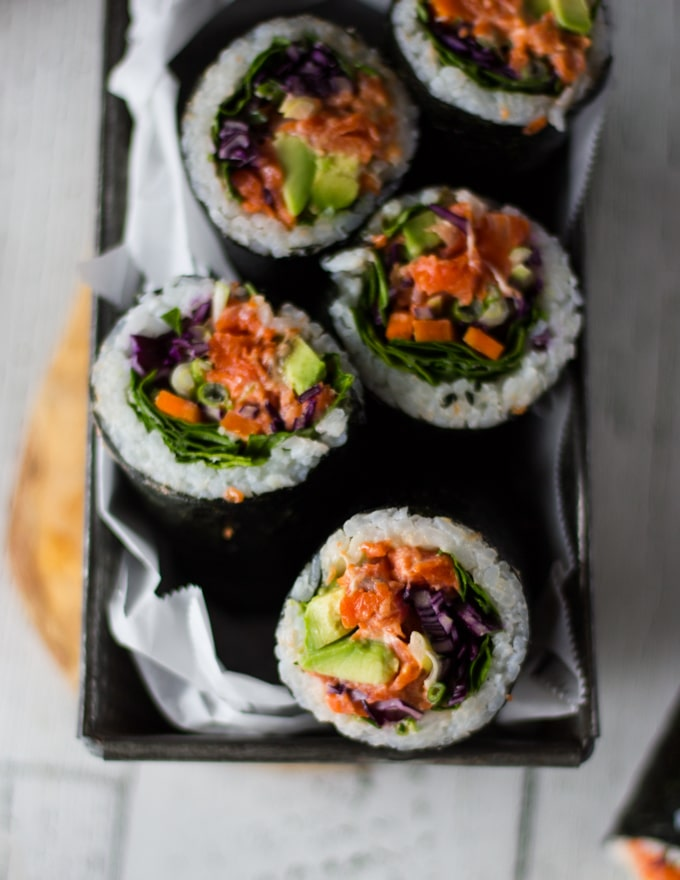 A plate with a few sushi burritos sliced up showing the fillings and layers in the roll close up