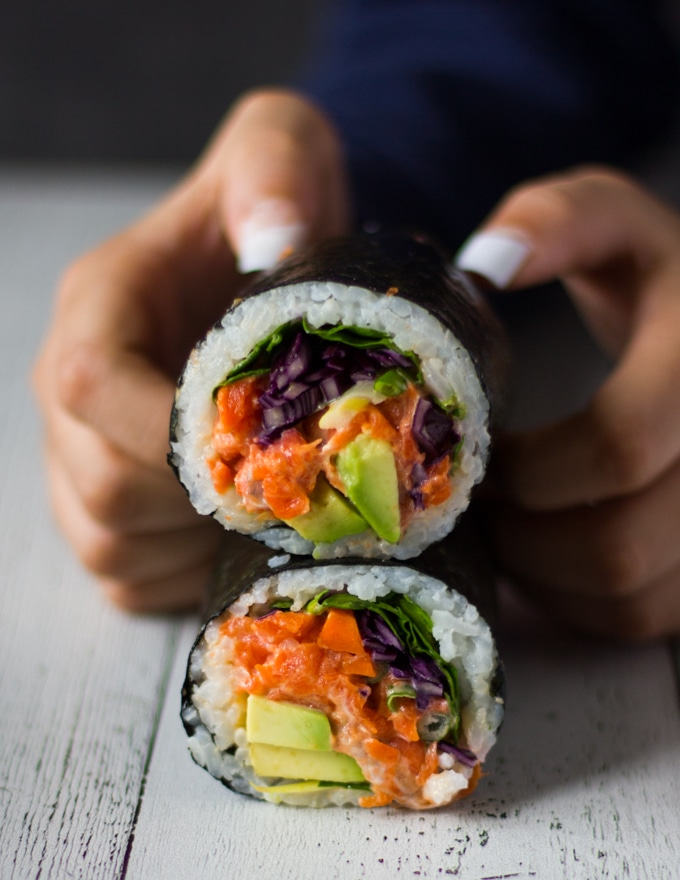 two hands trying to hold one sushi burrito sliced in half over a white board