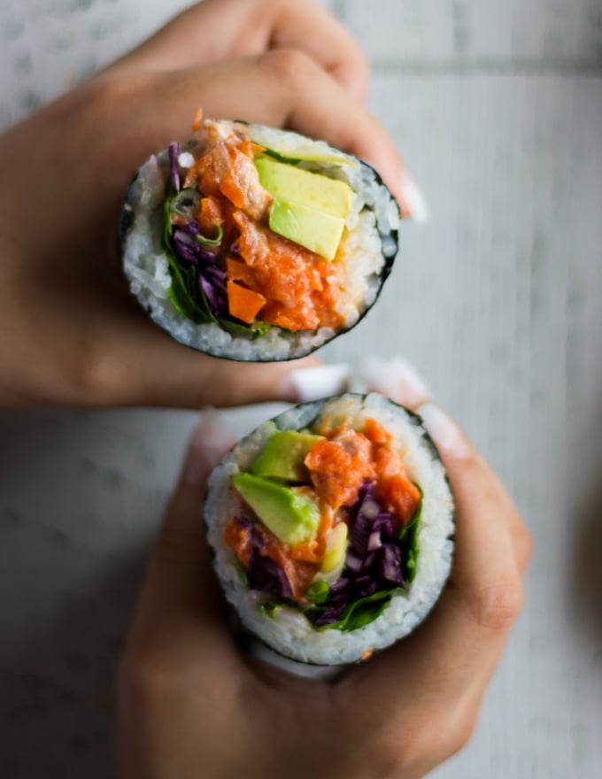 two hands holding off two halves of the sushi burrito pointing up and showing the contrast in colors of the fillings and the sushi rice and all the layers
