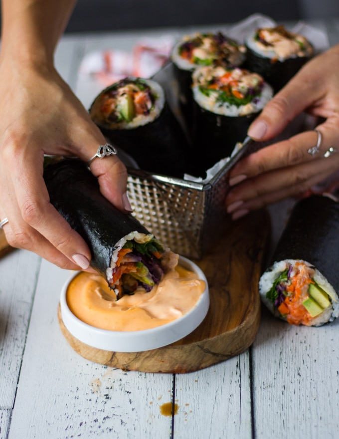 A hand dipping a sushi burrito into more spicy mayo
