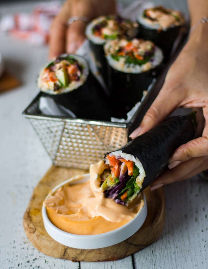 A hand dipping more sushi burrito into the spicy mayo and biting