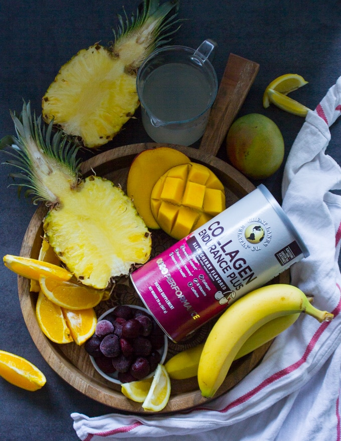 A wooden tray with all the tropical fruits used in the tropical smoothie such as half a pineapple, mangoes, cherries, banana, orange segments and coconut water and a box of collagen to boost the smoothie