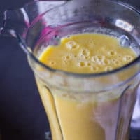 Final mango banana smoothie or pineapple smoothie layer ready in a blender
