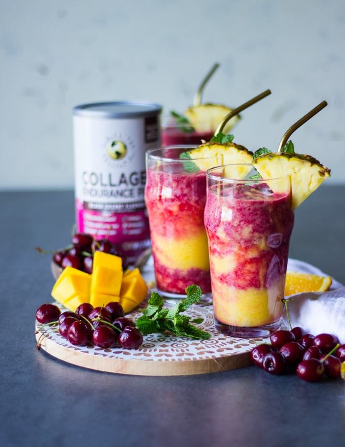 two thick tropical smoothie cups on a white wooden board surrounded by fresh cherries and mangoes with two straws and sliced pineapple for garnish