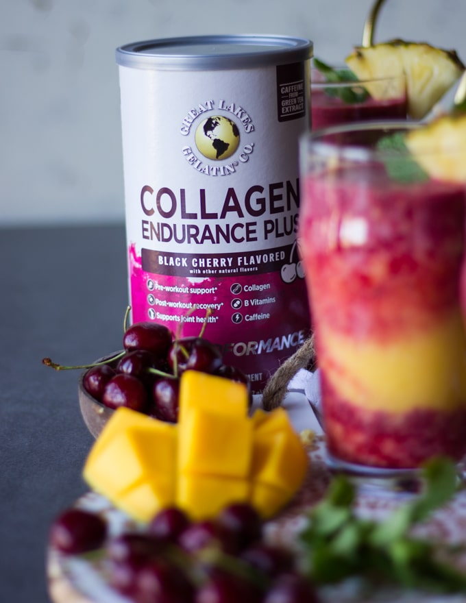 A box of collagen to thicken the smoothies and a hazy cup of tropical smoothie and some tropical fruits and fresh mint on a wooden board