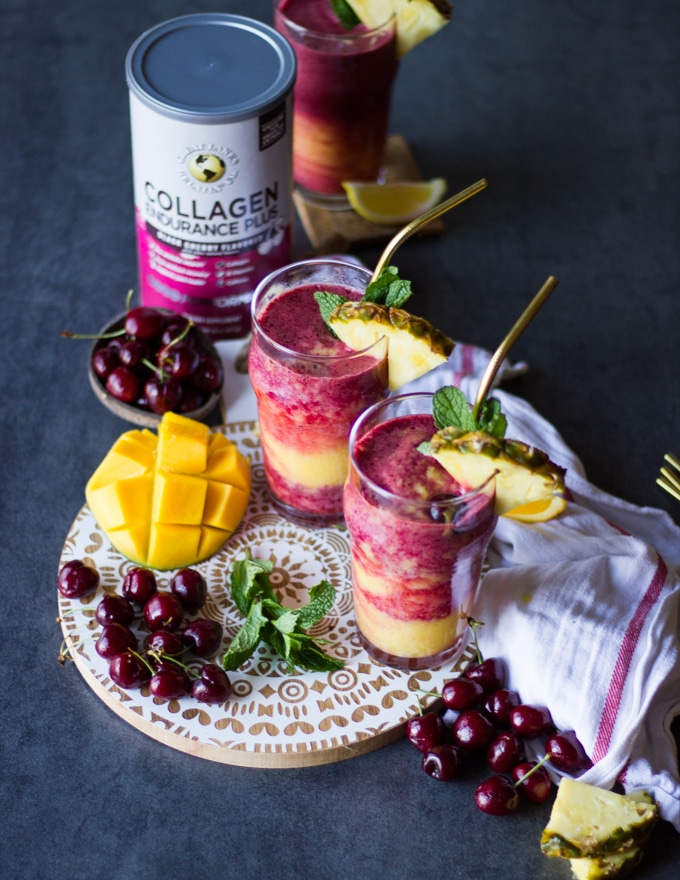 A board with a white wooden top and three cups of tropical smoothies with straws over it, each smoothie garnished with fresh pineapple and surrounded by tropical fruits and a tea towel and the collagen box