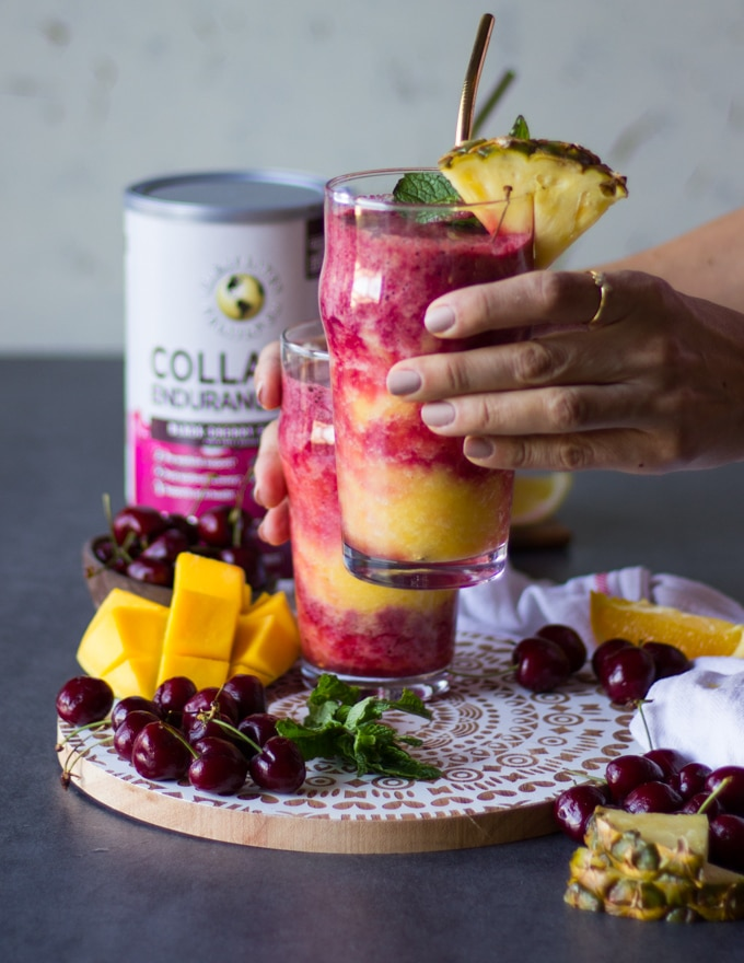 A hand holding up a cup of tropical smoothie highlighting the layers of smoothies. Some fruit surrounded the table like fresh cherries and mangos