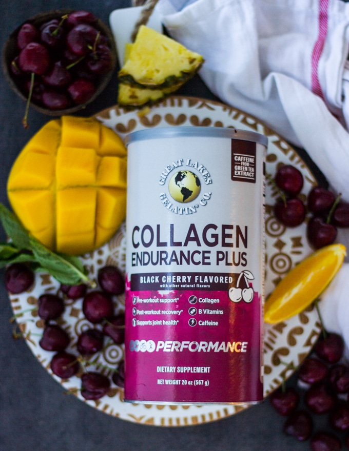 A box of GLG Collagen Endurance surrounded by fresh cherries, mangoes, pineapple slices and an orange segment on a white wooden board