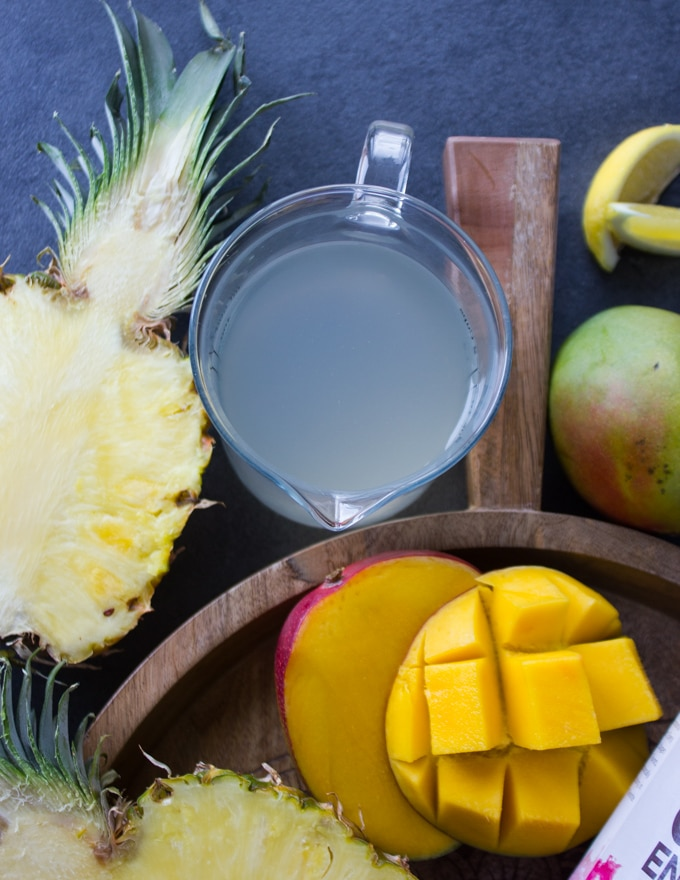A cup with coconut water surrounded by tropical fruits like half a sliced pineapple and mangos.