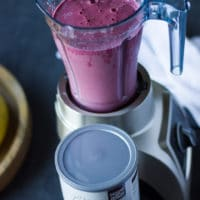 A blender with the cherry smoothie layer finished and thick