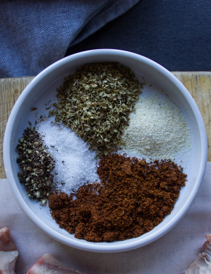 A plate with seasoning spices including salt, pepper, chilli powder, oregano and onion powder