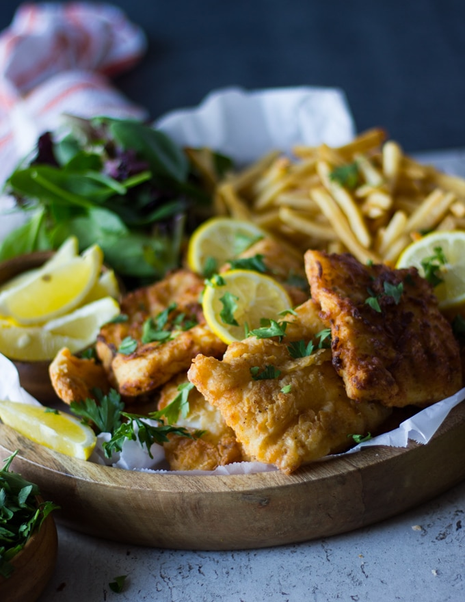 A finished plate of fish fry and fries on a wooden board surrounded by lemon slices and sprinkled with parsley