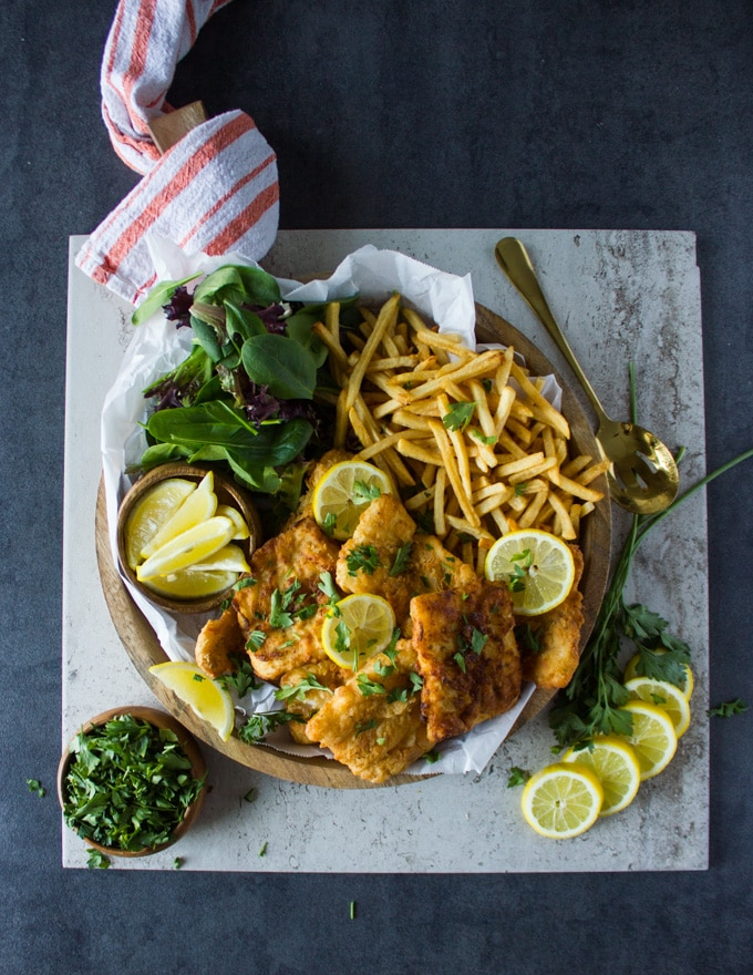 A huge platter with fish fry, lemon wedges, french fries and salad on a wooden board over a marble surrounded by lemon slices and a bowl of parsley