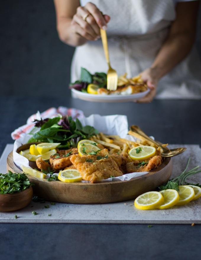 A huge plate of fish fry, french fries, greens with lemon slices and at the back someone holding a plate of fried fish and eating it with a fork