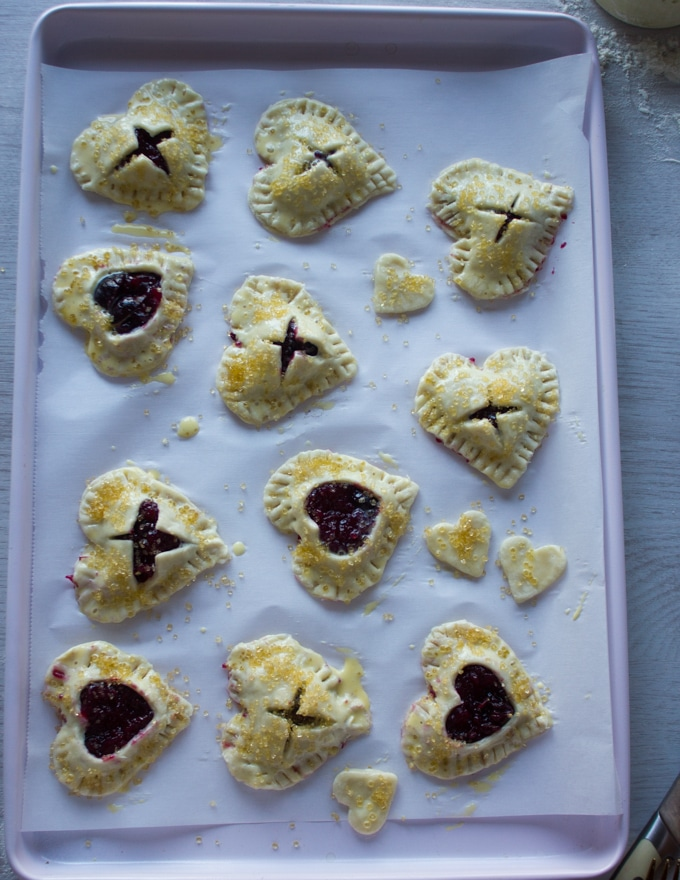 A tray of mini cherry pies going into the oven