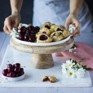 A stand with a white plate filled with mini cherry pie and some fresh cherries on the side, a pink napkin and white flowers. Two hands holding the plate.