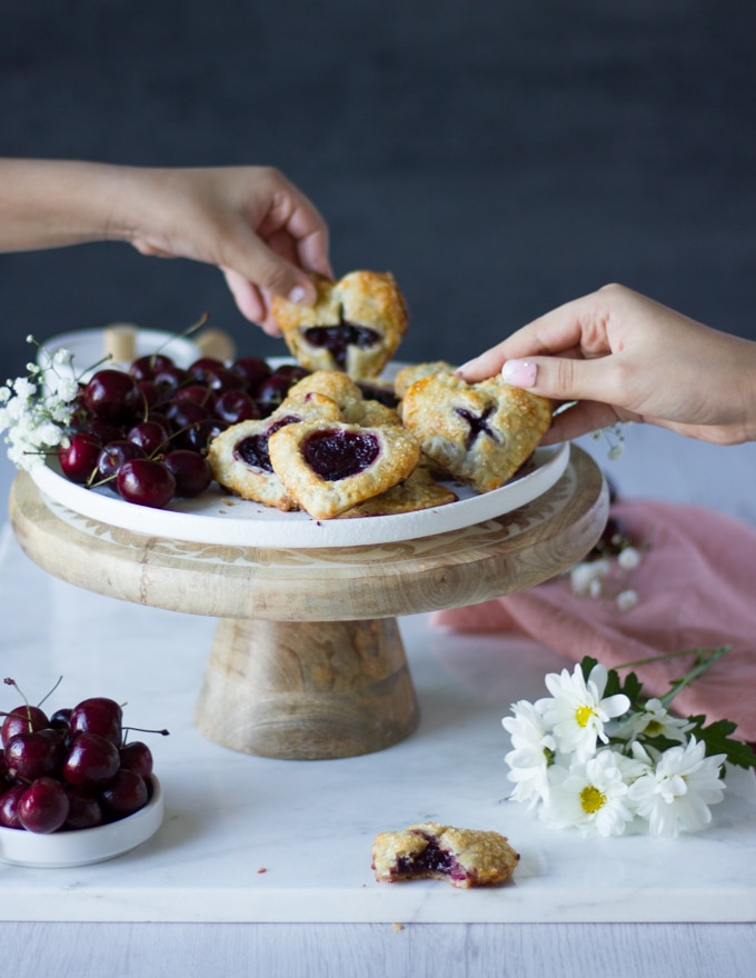 two kids hands grabbing the cherry pies from a serving plate on a white marble surrounded by white flowers and a pink tea towel