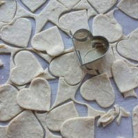 a heart cookie cutter cutting out the pie dough into small pies