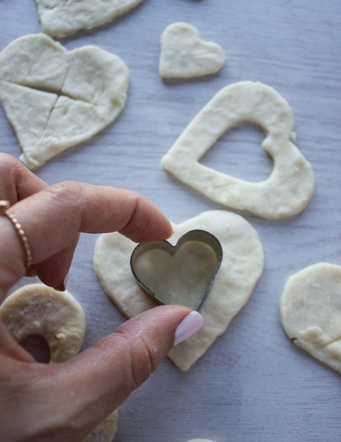 A hand cuting out smaller heart shapes on the tops of the pie crusts for cherry pie