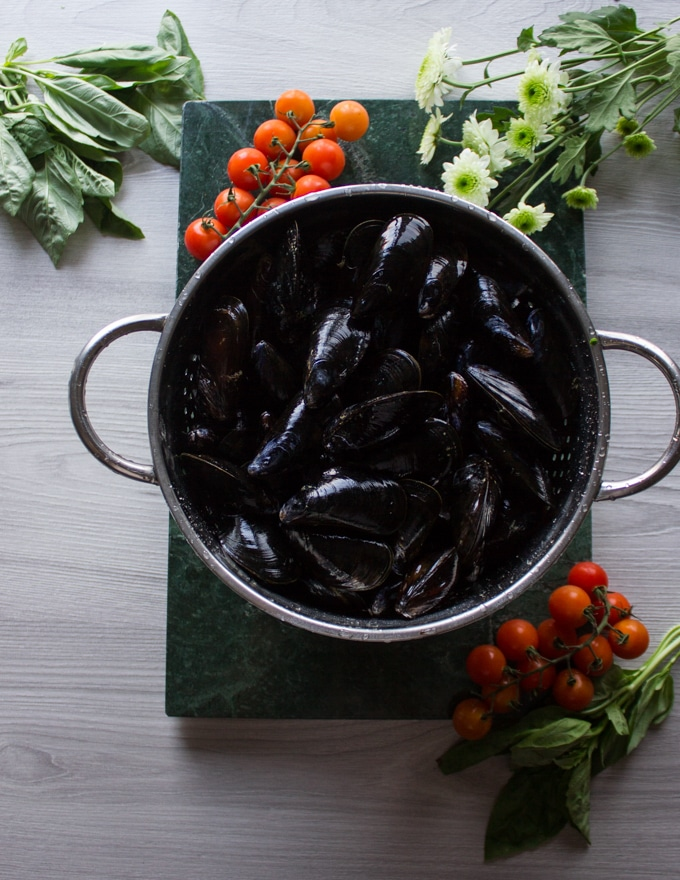 A colander of fresh mussels on a green marble surrounded by basil and fresh and tomatoes