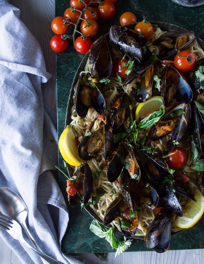 A huge plate of mussels marinara on a green marble ad pasta for mussels pasta and fresh basil