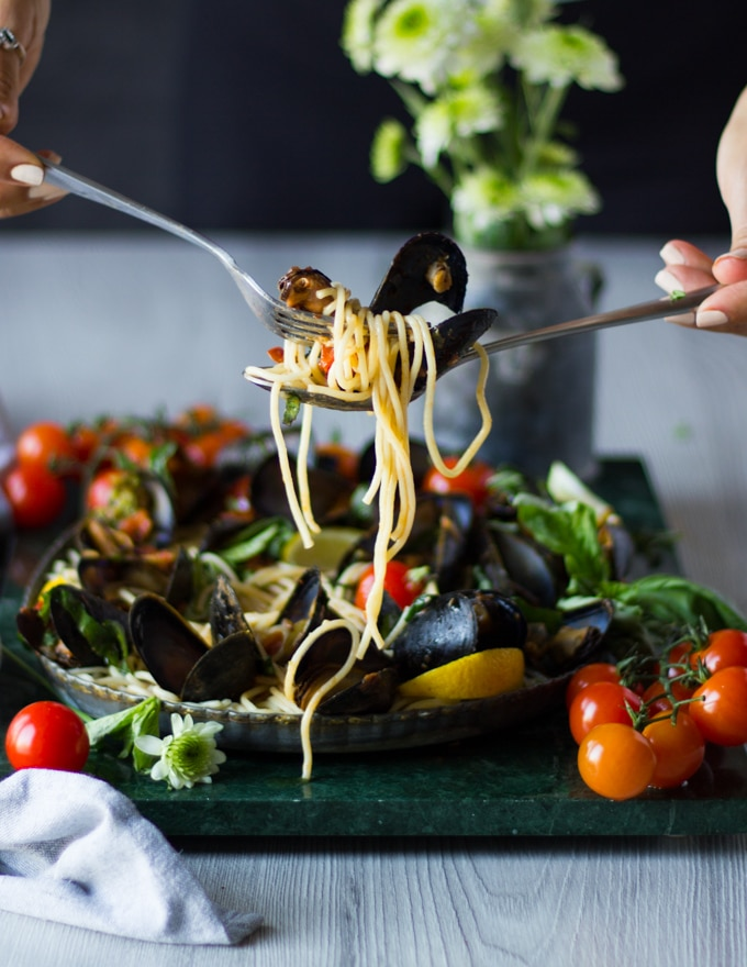 two hands with spoons and forks holding off pasta from a plate with mussels marinara and mussel pasta