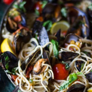 Close up of a spoon in a bowl of mussels pasta showing the tomato marinara sauce, the cooked mussels, the fresh basil and lemon wedges