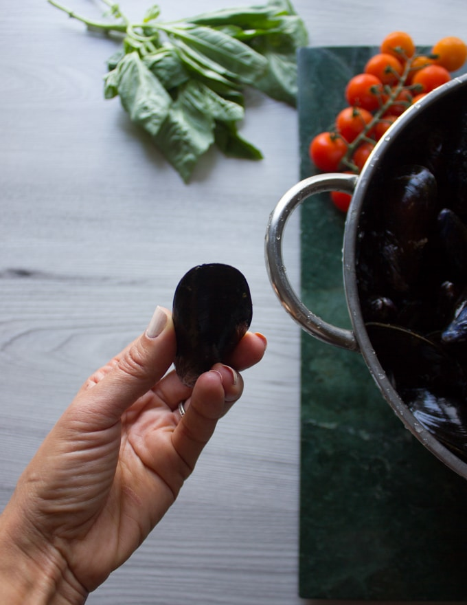 A hand holding a cleaned and closed fresh mussel before cooking