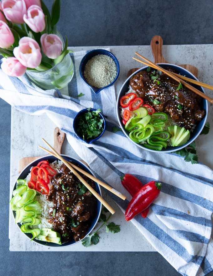 2 ready made bowls of beef tips and rice with a blue towel and some pink tulips, a bowl of cilantro and sesame seeds, some avocado slices and chopsticks to serve