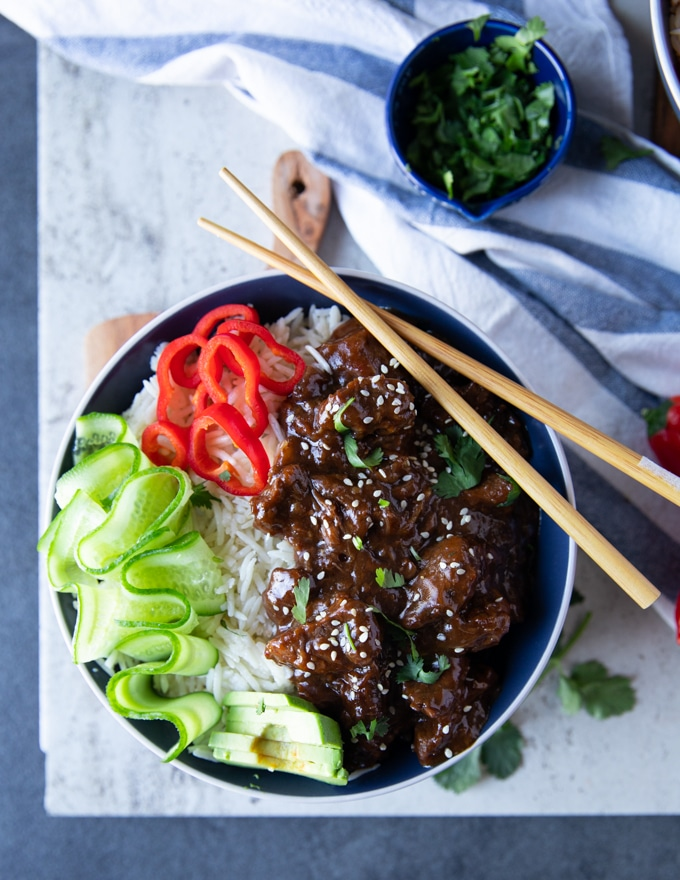 A bowl of beef tips and rice with chopsticks, cucumber rounds red bell peppers and cilantro in a small bowl with a blue towel on the side