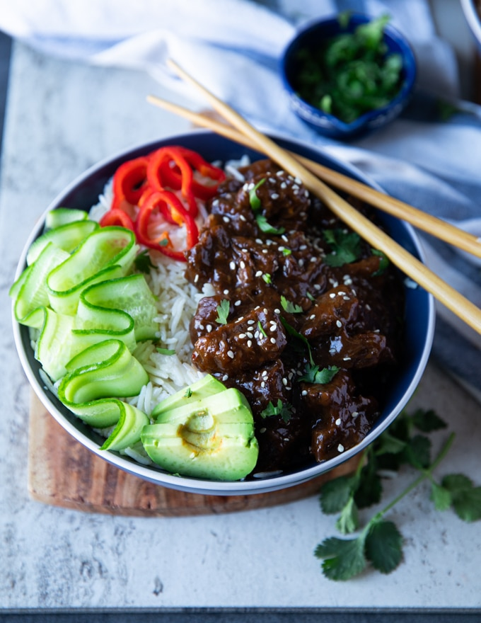 Close up of a single bowl of beef tips recipe and rice showing the texture of the cooked beef tips and the rice