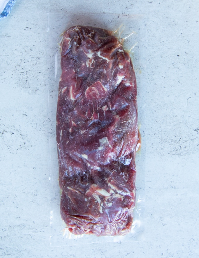 A block of frozen beef tips ready to defrost