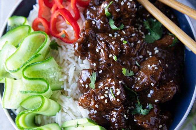 A bowl of beef tips and rice with chopsticks, cucumber rounds red bell peppers and cilantro