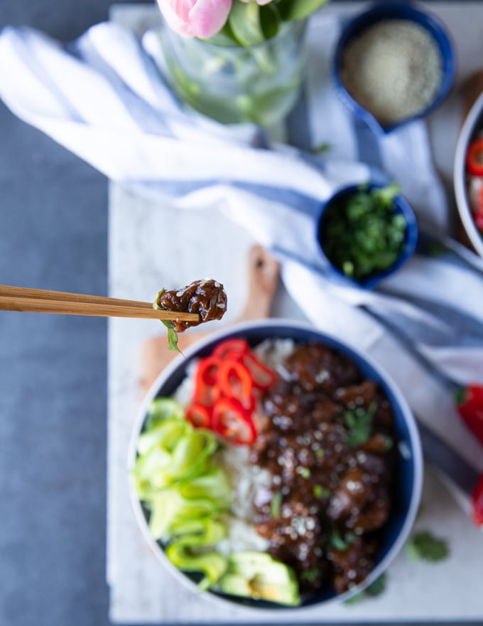 One chop stick holding a beef tip over a bowl of beef tips and rice showing the texture and sauce of the beef tips