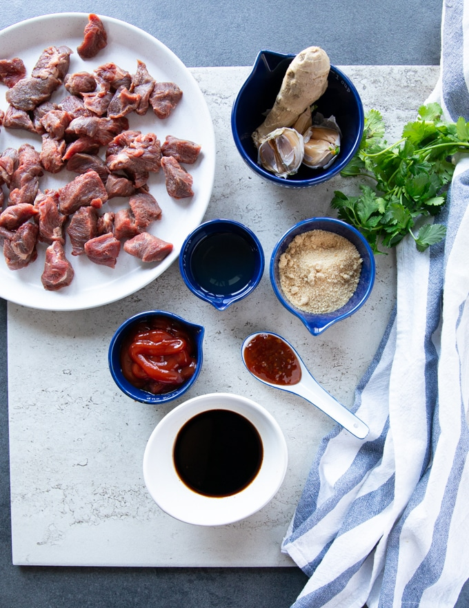 Ingredients for beef tips recipe: beef tips on a plate, fresh ginger and fresh garlic, brown sugar, ketchup, soy sauce, rice vinegar, chilli sauce, cilantro