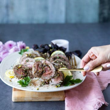 A hand holding a spoon serving one piece of the sliced roasted leg of lamb showing the lamb