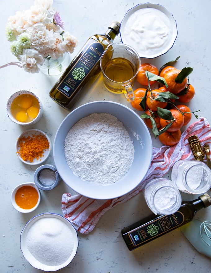 A list of ingredients for the olive oil cake showing a bowl of flour, another bowl of sugar, a cup of olive oil, some clementine or orange zest and juice, a bowl of yogurt and a bowl of eggs, also jars of baking powder and baking soda