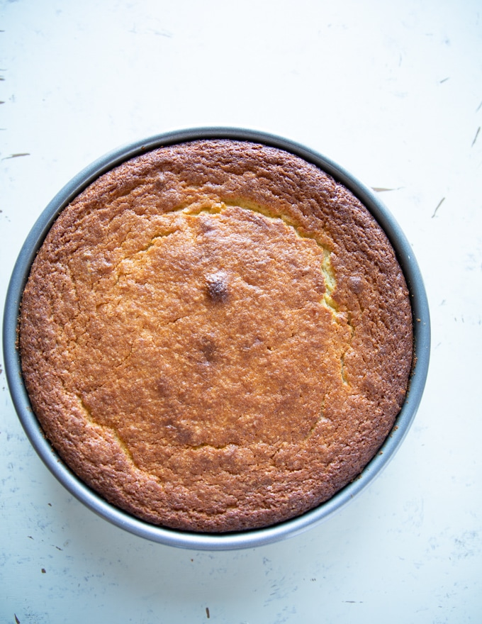 golden yellow olive oil cake right out of the oven and ready for an olive oil brushing